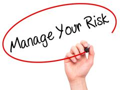 Man Hand writing Manage your Risk with black marker on visual screen - stock photo