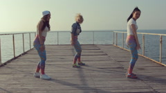 Three teenage girls dancing dance hall on the docks near sea Stock Footage