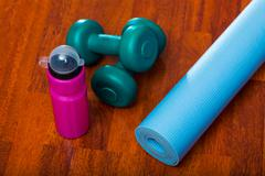 Two dumbbells with water bottle and yoga mat, sporty lifestyle concept - stock photo
