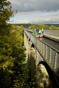Narrowboat crossing the River Dee in autumn on the Pontcysyllte Aqueduct, built - stock photo