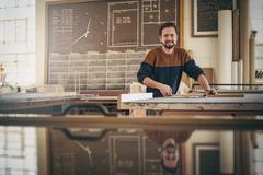 Smiling craftsman at work in his woodwork studio Stock Photos