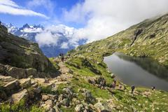 Low clouds and mist around Grandes Jorasses and Mont Blanc while hikers proceed - stock photo