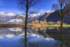The natural reserve of Pian di Spagna flooded with snowy peaks reflected in the - stock photo