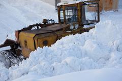 Tractor with scraper removes snow - stock photo