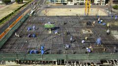 Workers scurry around rebar frame, construction floor before concrete pumping Stock Footage