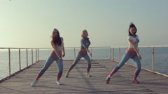 Booty dance by girls teenager on a wooden berth at the sea Stock Footage