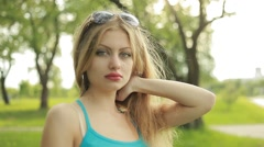 Young beautiful long-haired blonde in the summer on the nature Stock Footage