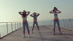 Three energetic girl dancing twerk on a wooden pier near the sea Stock Footage
