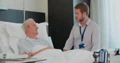 Senior Male Patient And Doctor Talking In Hospital Room - stock footage