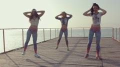 Energetic twerk by trendy teen girls on a wooden pier near the sea Stock Footage