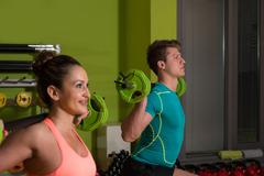 Young Couple Doing Exercise Barbell Squat - stock photo