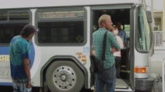 People boarding a bus in the city Stock Footage