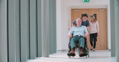 Nurse Pushing Senior Patient In Wheelchair Along Corridor - stock footage