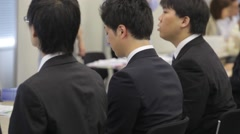 Male college students in dark suits during a job fair in Tokyo Japan Stock Footage