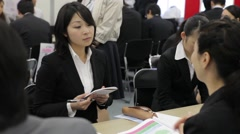 A female college student in dark suit nods during job interview in Tokyo Japan Stock Footage