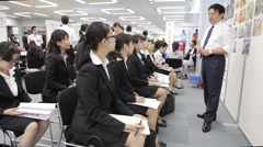 Female college students listen to a male recruiter at job fair in Tokyo Stock Footage