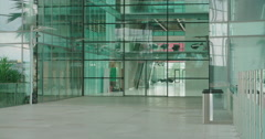 Panning shot down the entrance of a modern business building - stock footage