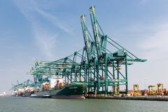 Harbor of Antwerp with cargo ships moored at quay with big cranes Stock Photos