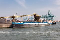 Harbor Antwerp with bargo moored at a quay with coal handling - stock photo