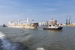 Tugboat with cargo ship in the harbor of Antwerp, Belgium - stock photo