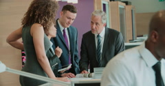 Business colleagues stand talking in a busy office, close up - stock footage