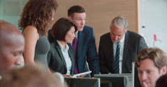 Business colleagues stand talking in a busy office, close up Stock Footage