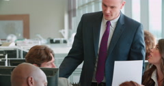 Manager talking with coworkers in an open plan office Stock Footage