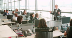 Senior male manager addressing workers in open plan office - stock footage