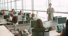 Male manager addressing workers in an open plan office - stock footage