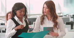 Two female coworkers discussing a document in a busy office Stock Footage