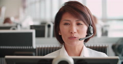 Chinese woman working in a call centre using a headset - stock footage