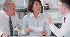 Three corporate colleagues meeting in an office, close up Stock Footage