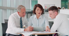 Three corporate colleagues meeting in an office - stock footage