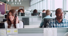 Male and female call centre workers wearing headsets - stock footage