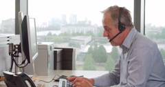 Senior male call centre worker wearing headset, side view - stock footage