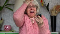 Happy old woman with cell phone - stock footage