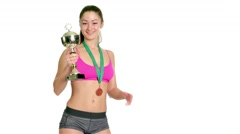 Happy sports woman holding winner cup and a medal isolated Stock Footage