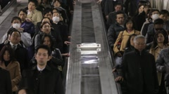 MEDIUM SHOT OF COMMUTERS ON ESCALATOR AT TRAIN STATION RUSH HOURS IN TOKYO Stock Footage
