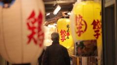 JAPANESE MAN WALKING IN TRADITIONAL RED LANTERNS BAR DISTRICT TOKYO Stock Footage