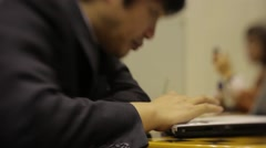 TIGHT SHOT OF A BUSINESSMAN WORKING ON HIS COMPUTER IN TOKYO JAPAN Stock Footage