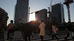 WIDE SHOT OF COMMUTERS CROSSING INTERSECTION SUNSET DURING RUSH HOUR IN TOKYO Stock Footage