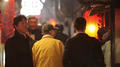 TIGHT SHOT OF JAPANESE BUSINESSMEN WALKING IN TRADITIONAL RED LIGHT TOKYO Stock Footage