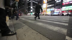 WIDE SHOT OF COMMUTERS CROSSING BUSY INTERSECTION DURING RUSH HOUR IN TOKYO Stock Footage