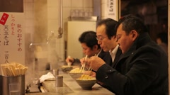 JAPANESE BUSINESS MEN EATING NOODLES IN RED LIGHT TOKYO Stock Footage