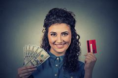 woman holding showing credit card and cash dollar banknotes bills - stock photo