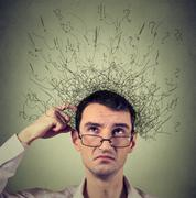 man scratching head, thinking with brain melting into many lines question mar - stock photo