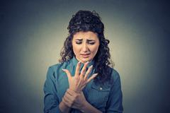 Young woman holding her painful wrist arm - stock photo