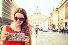 woman standing in front of basilica di san pietro in vatican city - stock photo