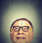 Portrait happy senior man in glasses with idea light bulb looking up. Stock Photos