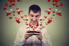 Handsome happy man sending receiving love sms text message on mobile phone Kuvituskuvat